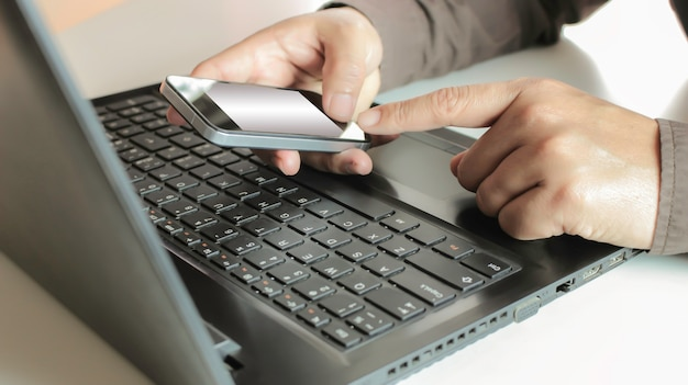 Hands using laptop and smartphone for online shopping