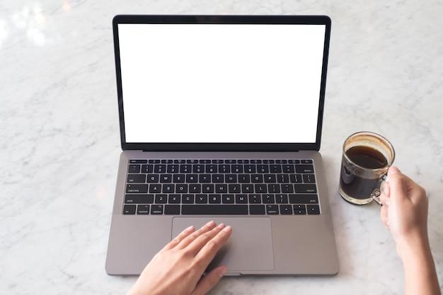Руки, используя ноутбук с пустой белый рабочий стол экрана, пить кофе на мраморный стол