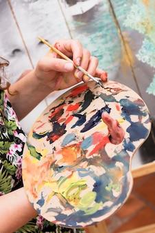 Mani usando la tavolozza di vernice