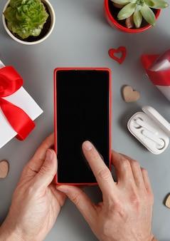 灰色のテーブルの上のギフトボックスとハートの近くでスマートフォンを使用して手