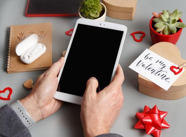 ギフトボックスの近くでタブレットを使用している手と灰色のテーブルの上の私のバレンタインカード