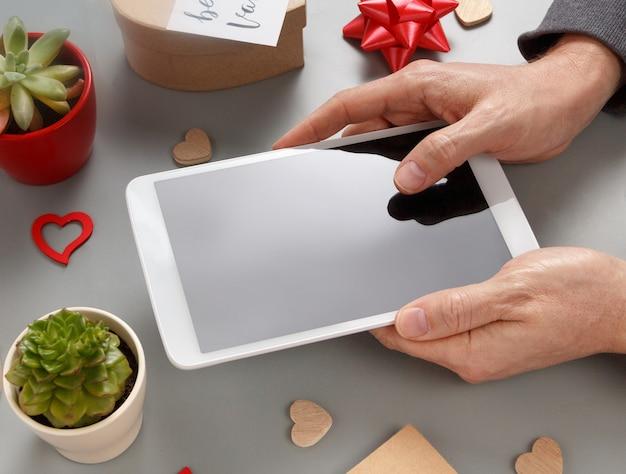 バレンタインデーの近くでタブレットを使用している手と灰色のテーブルの上の私のバレンタインカードの上面図