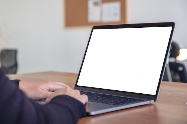 Hands using and typing on laptop with blank white desktop screen while sitting in office
