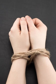 Hands of a victim woman tied up with rope