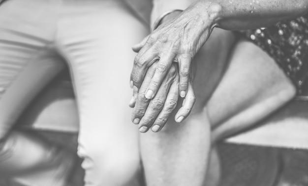 Руки вид пожилые супружеские пары, имеющие нежные моменты на открытом воздухе - зрелые люди за пределами сидя в скамейке