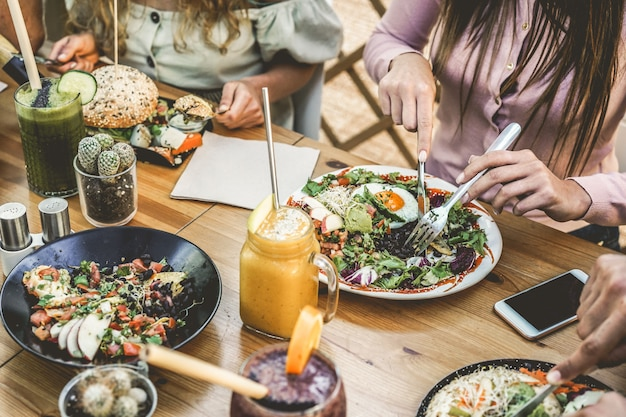 Hands view of young people eating brunch and drinking smoothies bowl with ecological straws in plastic free restaurant - healthy lifestyle, food trends concept - focus on top fork dish
