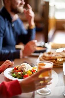 Hands view of young people eating brunch in trendy bar restaurant - healthy lifestyle, food trends concept - focus on left woman hand, dish