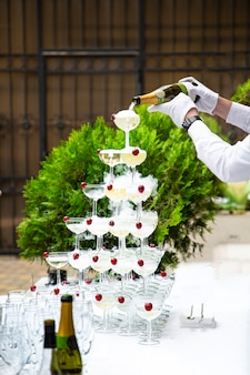 The hands of a waiter in white gloves pour champagne from a bottle into a pyramid of glasses at a buffet table
