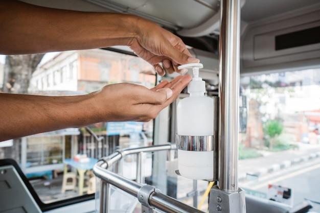 Мытье рук с помощью автоматического дозатора дезинфицирующего средства в общественном транспорте