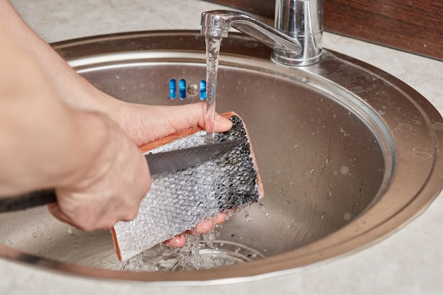Hands washing and cleaning salmon fish over kitchen sink