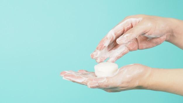 민트 그린 또는 티파니 블루 배경에 바 비누와 거품으로 손을 씻는 제스처.