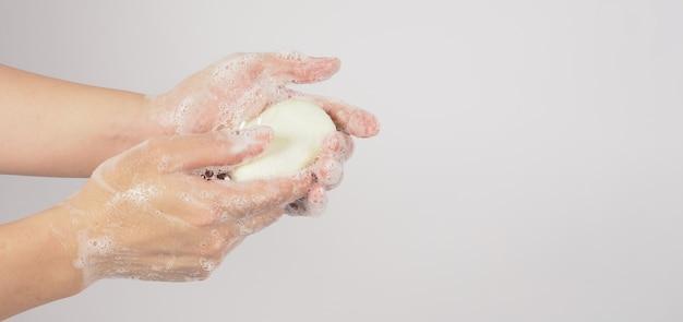 흰색 바탕에 비누와 거품으로 손을 씻는 제스처.