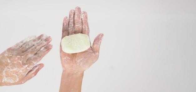 흰색 바탕에 비누와 거품 거품으로 손을 씻는 제스처.