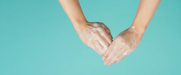 민트 그린 색상 또는 티파니 블루 배경에 거품 손 비누로 손을 씻는 제스처.