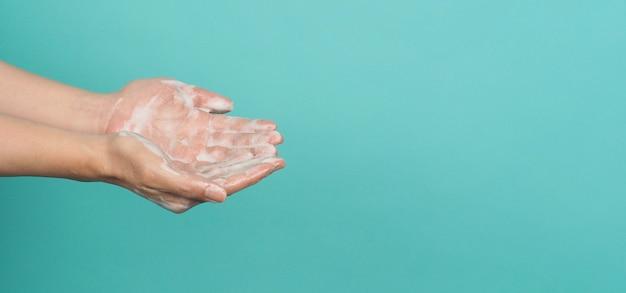 민트 또는 티파니 블루 배경에 거품 손 비누로 손을 씻는 제스처.