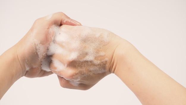 흰색 바탕에 거품 손 비누로 손을 씻는 제스처.
