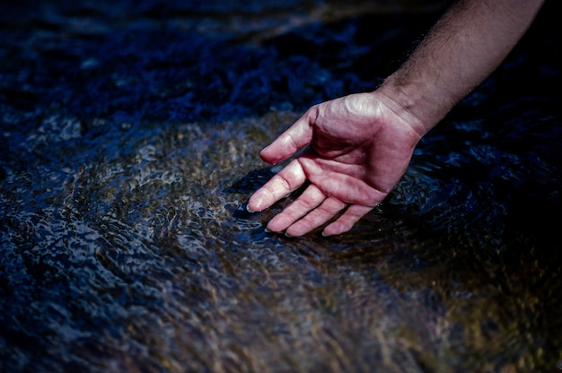 Hands and water flowing from natural waterfalls water