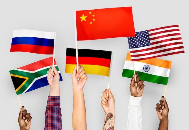 Mani che sventolano bandiere di cina, germania, india, sud africa e russia