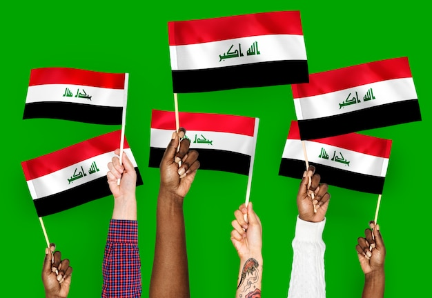 Hands waving flags of iraq