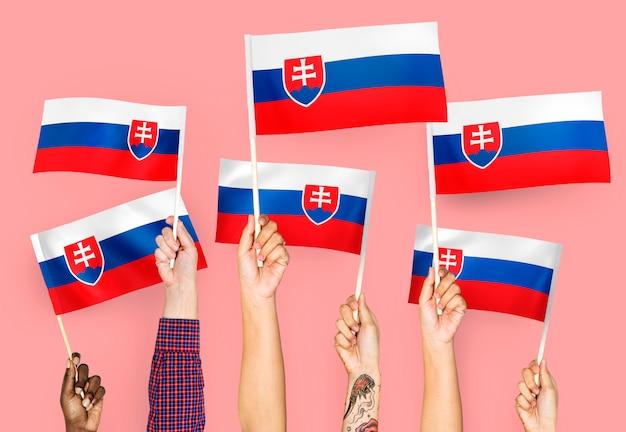 Руки машут флагами словакии