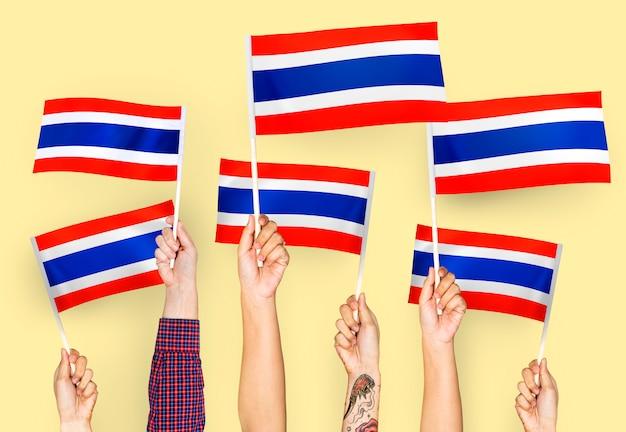 Руки размахивают флагами таиланда