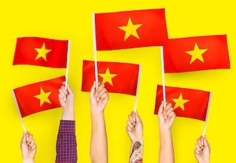 Hands waving flags of Vietnam