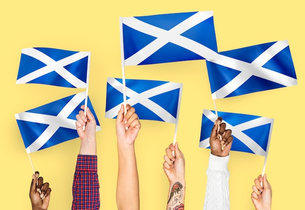 Hands waving flags of scotland
