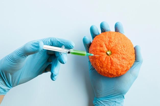 Mani indossando guanti e iniettando sostanze chimiche in un'arancia