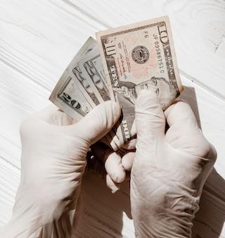 Mani che indossano guanti protettivi e dollari vista dall'alto