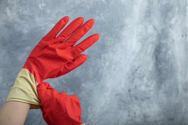 Hands wearing red protective gloves on marble.