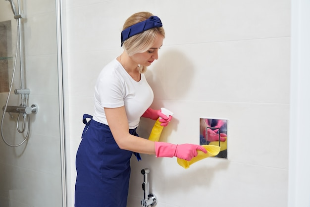 Руки в резиновых защитных перчатках чистят кнопку смыва унитаза. концепция дезинфекции