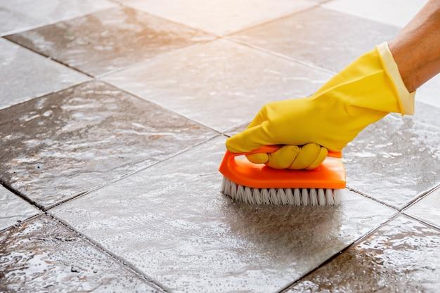 노란색 고무 장갑을 끼고 손이 플라스틱 바닥 수세미를 사용하여 바닥 청소제로 타일 바닥을 문지르고 있습니다.