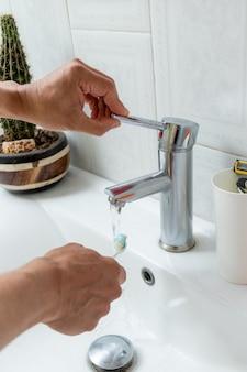 Руки смачивают зубную щетку