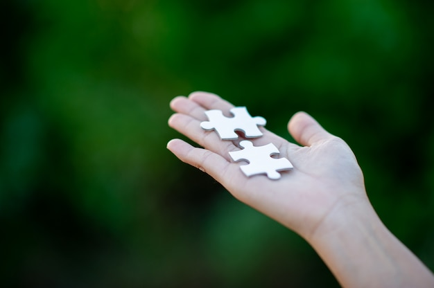Hands and white jigsaw puzzles
