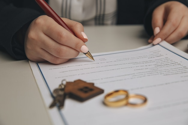 Hands of wife, husband signing decree of divorce, dissolution, canceling marriage, legal separation documents