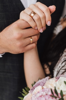 Hands of a wife and a husband with wedding and engagement rings and part of floral bouquet