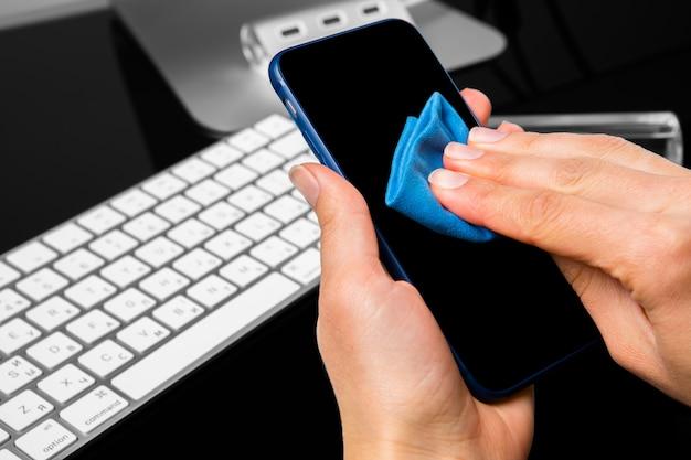 携帯電話を布で拭く手