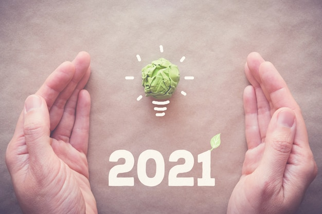 Hands with 2021 and green paper light bulb
