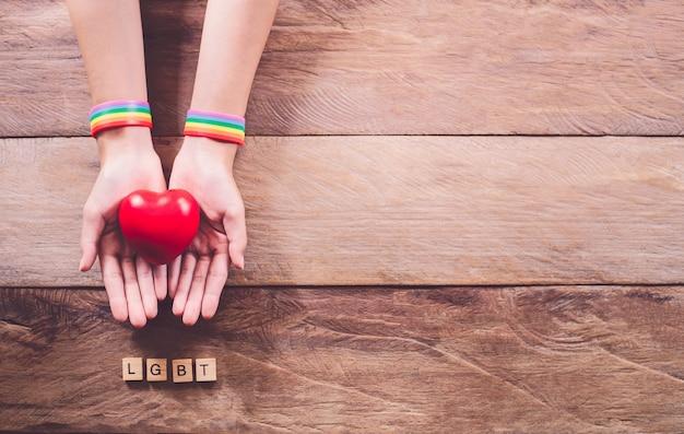 虹色のリストバンドが付いている手は木の床に置かれます。ゲイの権利の戦い。ゲイプライドlgbtの概念