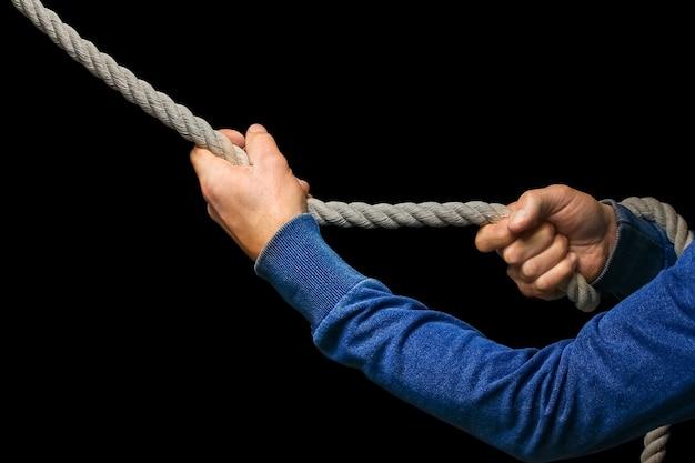黒い壁にロープを持った手。男はロープレスリングを引っ張る。ビジネスをあなたの側にドラッグします。