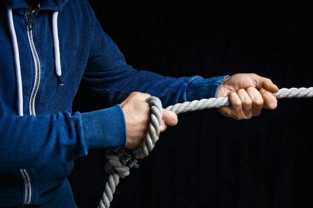 黒い壁にロープを持った手