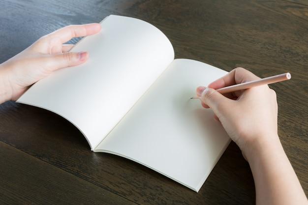 Руки с открытой пустой блокнот и карандаш