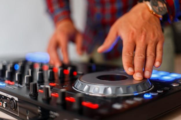 오디오 컨트롤이있는 손. 믹싱 트랙. 전문 컨트롤러