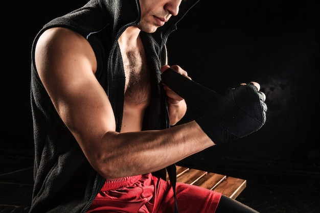Hands with bandage of muscular man training kickboxing  on black