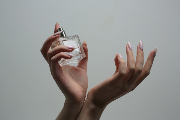 Hands with a beautiful manicure hold a bottle with perfume on a gray background. close-up