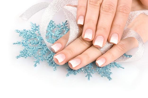 Руки с красивым зимним дизайном, снежинками и лентой solated на белом