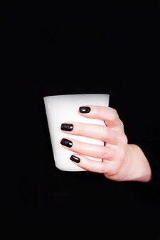Руки с черным маникюром, держа белую чашку