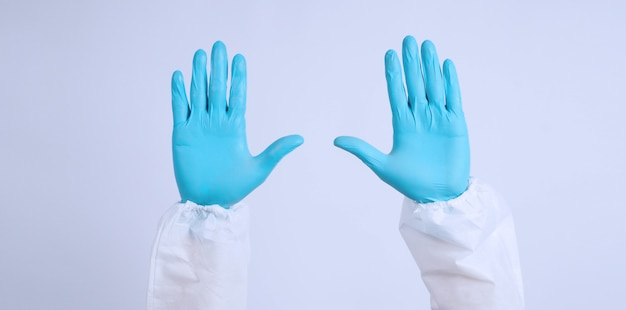 Hands with blue gloves and ppe suite on white background.