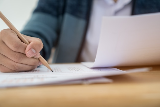 Hands with blue pen over application form, students taking exams, writing examination