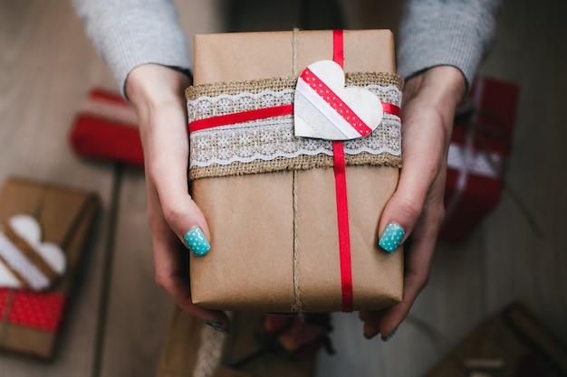 Mani con un pacchetto marrone con un cuore